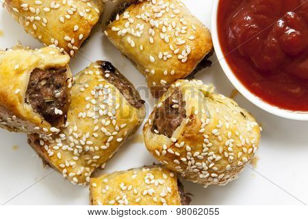 Homemade sausage rolls with sesame seeds and tomato sauce.
