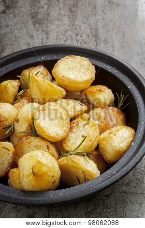 Roast Potatoes with rosemary and sea salt, in black serving dish.