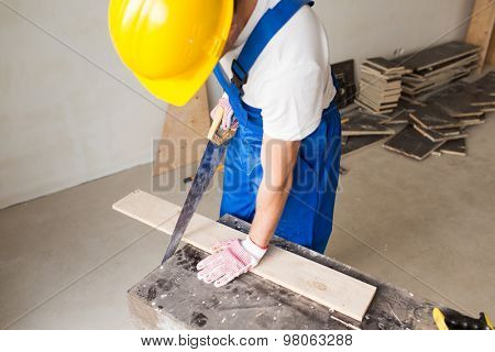 building, carpentry, repair, teamwork and people concept - close up of builder with arm saw sawing board on table
