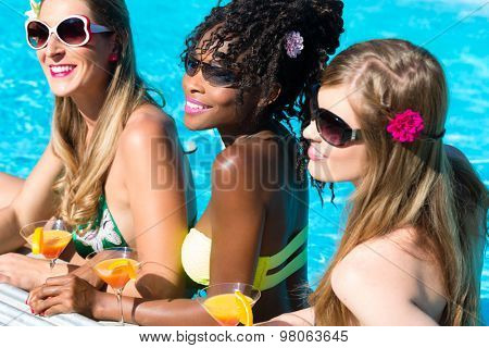 Three women friends drinking cocktails in swimming pool bar, African and Caucasian girls