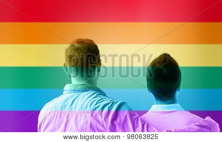 people, homosexuality, same-sex marriage, gay and love concept - close up of happy male gay couple or friends hugging from back over rainbow flag stripes background