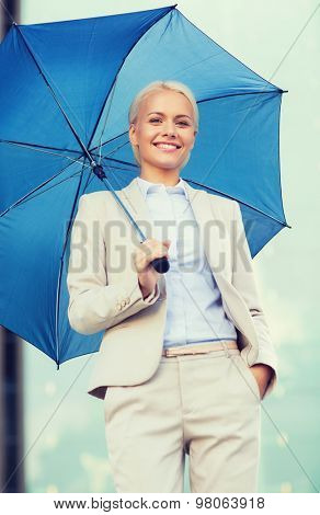 business, bad weather and people and concept - young smiling businesswoman with umbrella outdoors