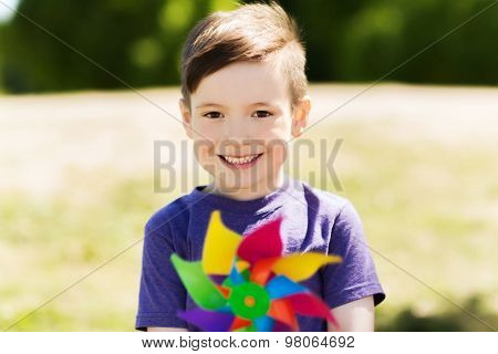 summer, childhood, leisure and people concept - happy little boy with colorful pinwheel toy outdoors