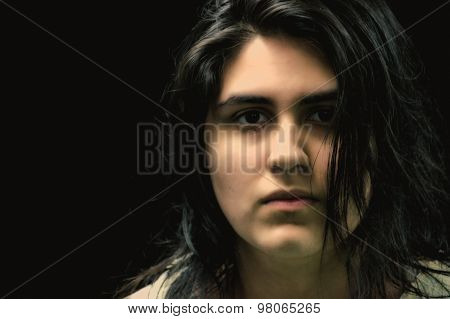 Latina teen in front of black background looking at camera