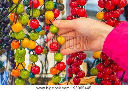 Hand Of Woman With Wooden Necklace On Stall At The Bazaar