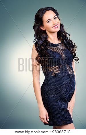 Fashion shot of a beautiful pregnant woman wearing elegant evening dress. Studio shot.