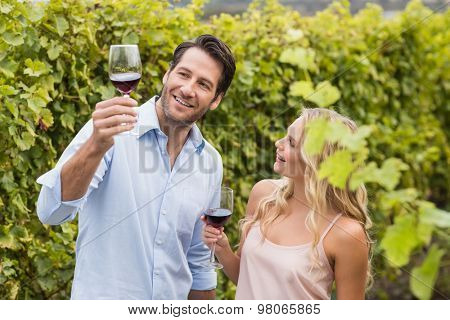 Young happy couple talking about wine in the grape fields