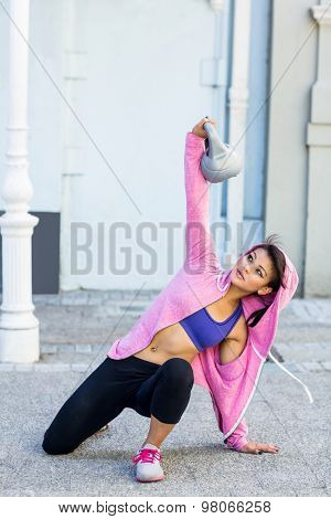Athletic woman exercising turkish get up with kettlebell in the city