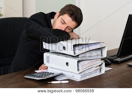 Businessman Sleeping On Binders