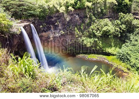 Beautiful Opaekaa Falls in Kauai Hawaii forms a rainbow when the sun angle contacts mist at the right time of day.W