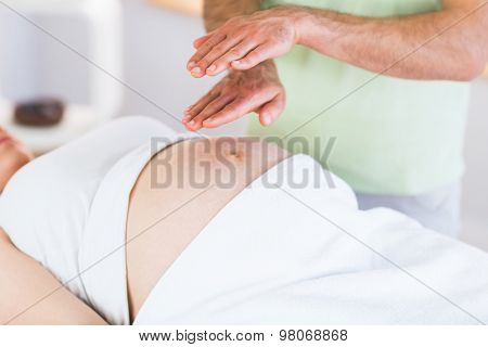 Close up view of pregnant woman getting reiki treatment in a studio