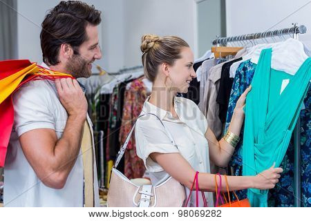 Smiling couple browsing clothes in clothing store