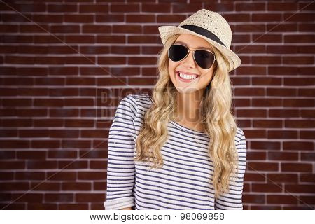 Portrait of gorgeous smiling blonde hipster with sunglasses and straw hat against red brick background