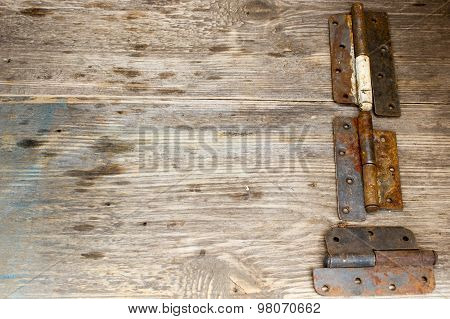 Metal Door Hinge On A Grungy Wooden Background,  Copy Space To Right.