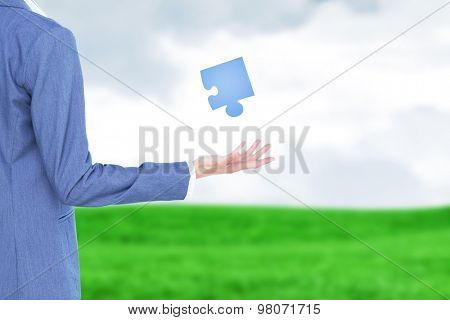 Businesswoman presenting against grey sky over field