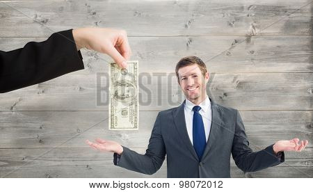Happy businessman with hands out against bleached wooden planks background