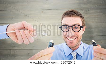 Geeky businessman holding two cables against bleached wooden planks background