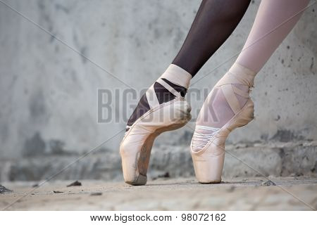 Ballerina feet close-up on a background of textured concrete wal