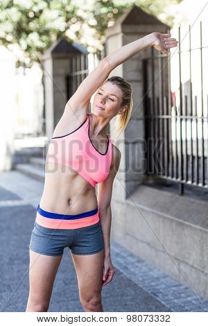 A beautiful woman stretching her arm next a fence on a sunny day