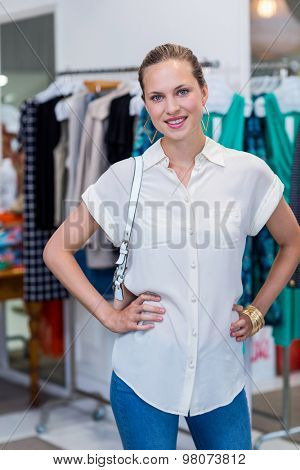 Portrait of smiling woman in front of clothes rail in clothing store