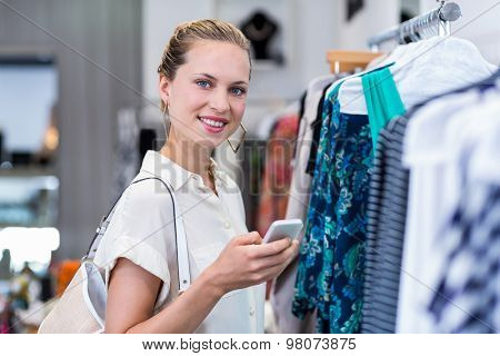 Portrait of smiling woman using smartphone in clothing store
