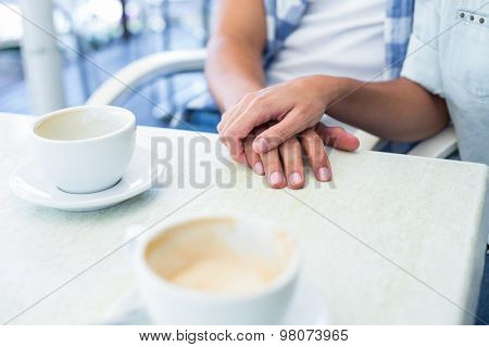 Cute couple on a date holding hands at the cafe