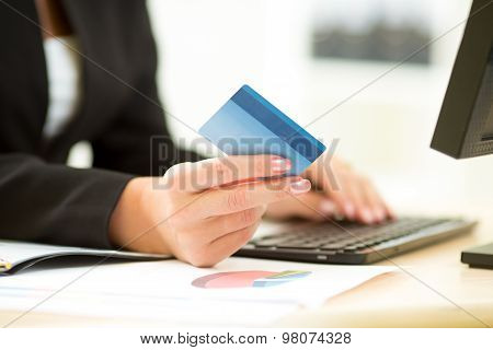 Business woman holding credit card in hand and entering security code using laptop keyboard