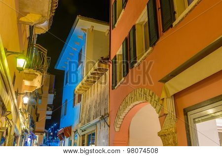 Narrow street of old apartment buildings at night in Malcesine, Italy.