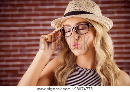 Gorgeous blonde hipster sending air kiss against red brick background