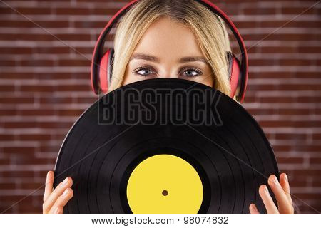 Portrait of a beautiful woman holding a vinyl against a brick wall