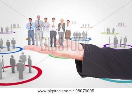Smiling business people applauding against human figures in circles