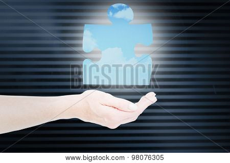 Hand presenting against blue sky