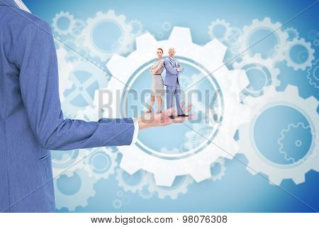 Serious businessman standing back to back with a woman against white wheels and cogs on blue