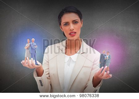 Serious businessman standing back to back with a woman against grey room