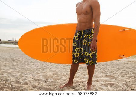 sea, summer vacation, water sport and people concept - close up of young man with surfboard on beach