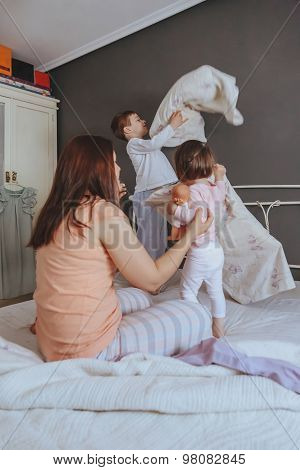 Relaxed mother and sons playing over the bed