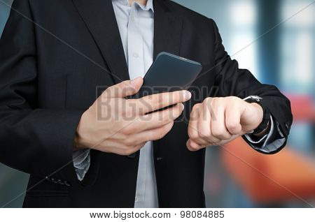 Businessman With Smartphone And Smartwatch In Office