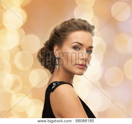 people, holidays, christmas and glamour concept - beautiful woman in evening dress wearing earrings over beige lights background