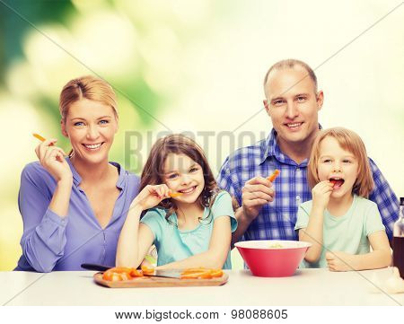food, family, children, hapiness and people concept - happy family with two kids eating at home