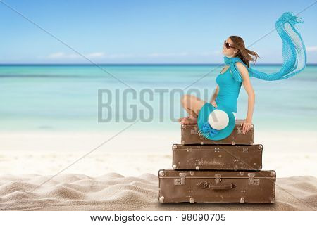 Pretty woman sitting on retro suitcases on beach. Concept of traveling