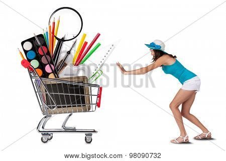 Girl refusing to basket full of school accessories, isolated on white background. Concept of education and start of new school year