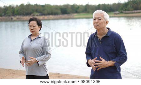 Asian Senior Elderly Couple Practice Taichi, Qi Gong Exercise Next To The Lake
