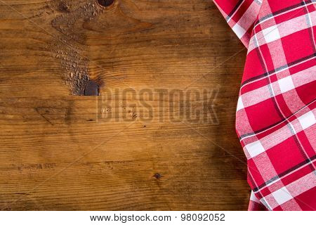 Top view of checkered napkin on wooden table.