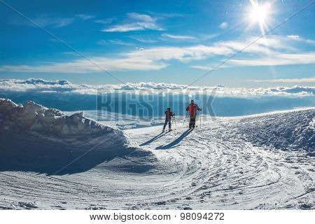 Two skiers on the peak of mountain in sunny day.
