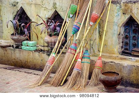 Detail Of Colorful Rustic Brooms Against Weathered Wall