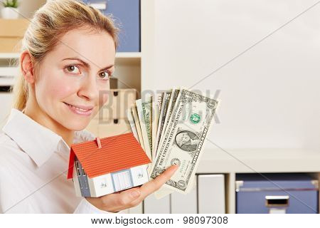 Smiling woman as real estate agent with small house and Dollar bills