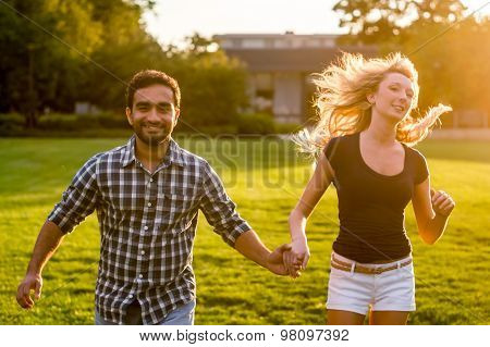 Interracial couple holding hands and running on field at sunset
