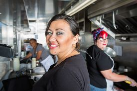 picture of food truck  - Three busy workers inside food truck preparing a meal - JPG