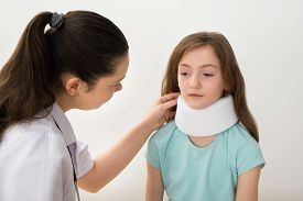 pic of neck brace  - Female Doctor Examining Neck Of Patient Wearing Neck Brace  - JPG