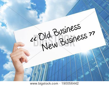 Old Business - New Business Sign On White Paper. Man Hand Holding Paper With Text. Isolated On Skysc
